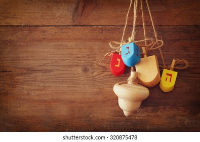 image of jewish holiday Hanukkah with wooden colorful dreidels (spinning top) hanging on a rope over wooden background