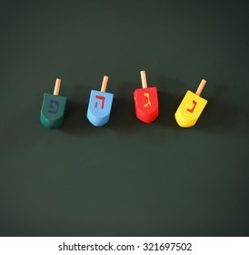 image of jewish holiday Hanukkah with wooden colorful dreidels (spinning top) over chalkboard background. room for text