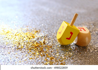 Image of jewish holiday Hanukkah with wooden dreidel (spinning top) on the glitter background