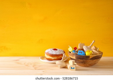 Image of jewish holiday Hanukkah with wooden dreidels colection (spinning top) and donut on the table