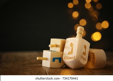 Image of jewish holiday Hanukkah with wooden dreidels colection (spinning top) and gold lights on the table