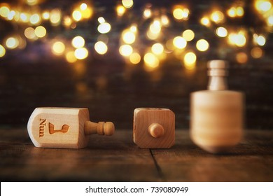 Image of jewish holiday Hanukkah with wooden dreidels colection (spinning top) and glowing gold lights on the table