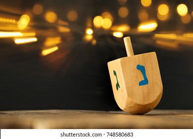 Image of jewish holiday Hanukkah with wooden dreidel (spinning top) and gold lights on the table