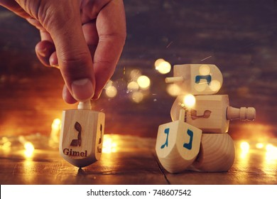 Image of jewish holiday Hanukkah with wooden dreidels colection (spinning top) and gold garland lights on the table.