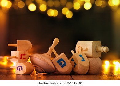 Image of jewish holiday Hanukkah with wooden dreidels colection (spinning top) and gold garland lights on the table