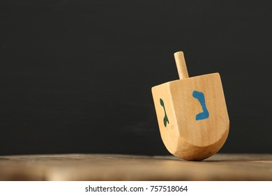 Image of jewish holiday Hanukkah with wooden dreidel (spinning top) on the table