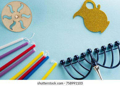 Image of jewish holiday Hanukkah with wooden dreidels (spinning top) , candles, menora (traditional Candelabra) , children's stickers glitter craft- jug of Chanukah on blue background.