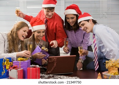 Image of joyful business group looking at screen of laptop and reading greets with smiles