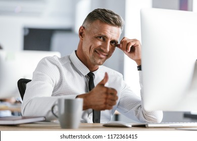 Image of joyful businessman 30s wearing white shirt and tie sitting at desk in office by computer and showing thumb up