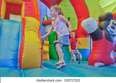 Image of joyful children who jumps on a big inflatable trampoline.
