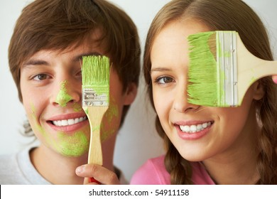 Image of joyful couple hiding one of eyes behind paintbrush with green color