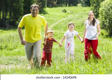 Image of joyful family running over green field holding each other by hands in summer