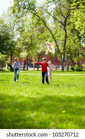 Image of joyful friends playing with kite outdoors