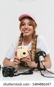Image of joyful girl recording blog broadcast with microphone about new photocamera isolated over white wall in studio