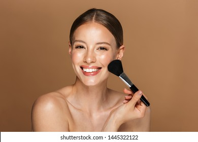 Image of joyful half-naked woman smiling at camera and using makeup brush isolated over beige background