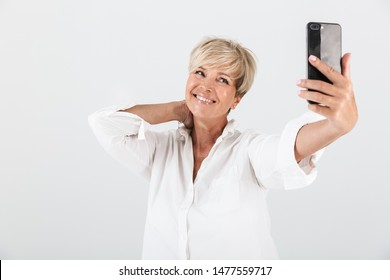Image of joyous adult woman with short blond hair smiling and taking selfie photo on cellphone isolated over white background in studio
