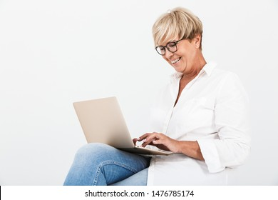 Image of joyous adult woman wearing eyeglasses smiling while sitting with laptop computer isolated over white background in studio