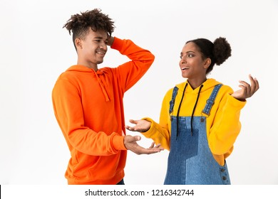 Image of joyous african american couple in colorful clothes smiling and talking isolated over white background