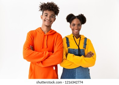 Image of joyous african american couple in colorful clothes standing with arms crossed isolated over white background