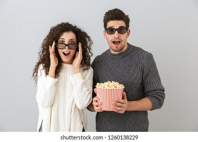 Image of joyous man and woman wearing 3d goggles holding bucket with pop corn isolated over gray background
