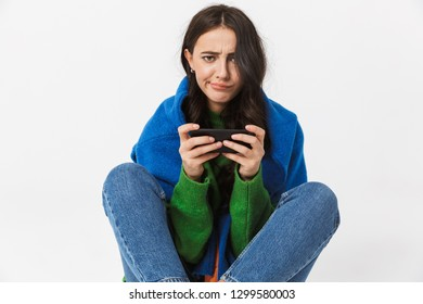 Image of joyous woman 30s in colorful clothes sitting on the floor and using cell phone isolated over white background