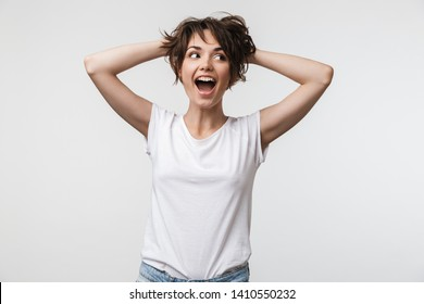 Image of joyous woman with short hair in basic t-shirt laughing and grabbing her head isolated over white background