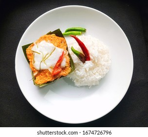 The image of a kind of healthy Thai food, steamed fish with curry paste and steamed rice on a white plate isolated on black background for decorative and design.