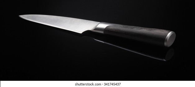 Image of kitchen knife with wooden handle on black background with reflection closeup