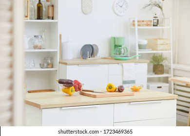 Image of kitchen table with wooden cutting board and fresh vegetables on it in the kitchen