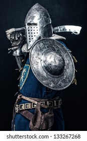 Image of knight who is holding his sword and shield while he is standing by his left side
