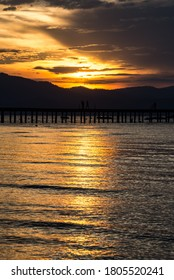 Image of a Lake Tahoe sunset with water reflection and silhouette of people walking on the dock.