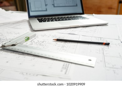 Image of laptop, pencil, calculator and a level ruler standing on top of architecture blueprint plan. Architect working place concept