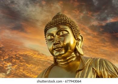 Image of a large golden Buddha at sunset
