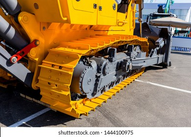 Image of a large new yellow bulldozer. Fragment of a caterpillar bulldozer.Powerful construction machinery