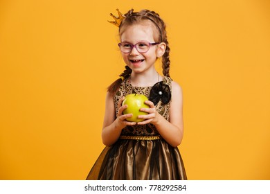 Image of laughing girl child wearing princess crown standing isolated over yellow background. Looking aside holding apple.