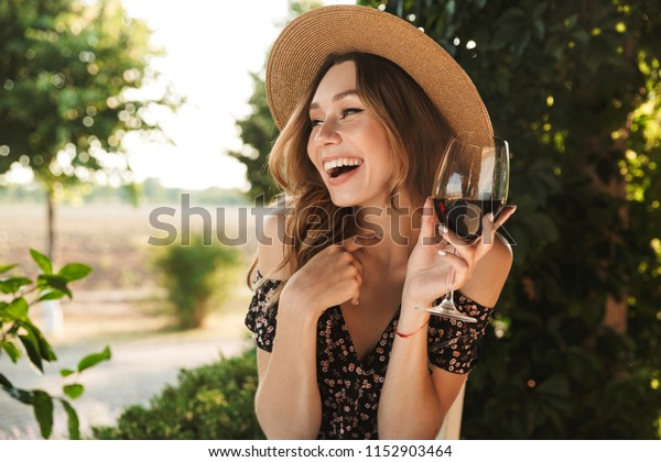 Image of laughing young woman sitting in cafe outdors in park holding glass drinking wine.