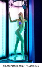 Image of leggy blonde tans in tanning booth