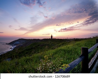 Image of a lighthouse during sunset with sky in the background.