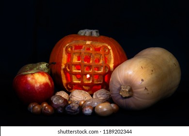 Image of a lit, carved Halloween pumpkin of the Celtic Samhain symbol with autumn/fall/harvest fruit, nuts and vegetables against a black background.