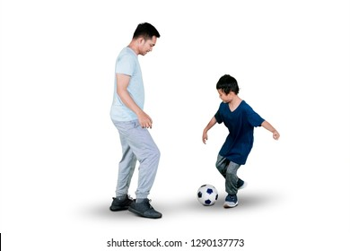 Image of little boy playing football with his father in the studio, isolated on white background