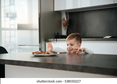 Image of little boy standing in kitchen while tries to take cookies and chocolate.