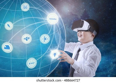 Image of little boy wearing virtual reality glasses and touching virtual screen with globe.Elements of this image furnished by NASA.