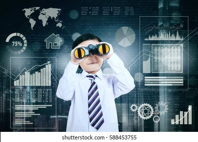 Image of a little businessman using a binocular while looking at the camera and standing with growth business in the background