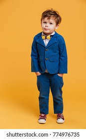 Image of little confused boy child standing isolated over yellow background. Looking camera.
