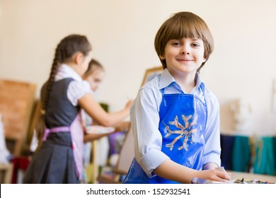 Image of little cute boy painting pictures at kindergarten