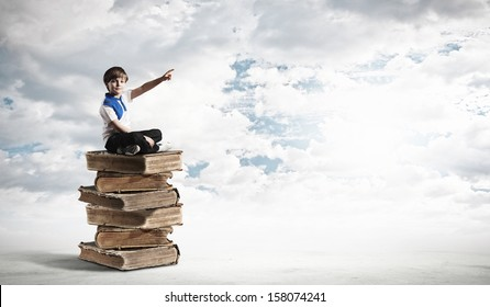 Image of little cute boy sitting on pile of books