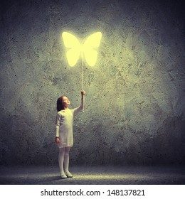 Image of little cute girl holding butterfly balloon