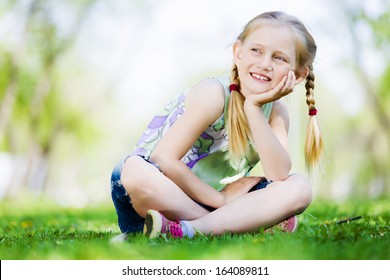 Image of little cute girl sitting on grass in park