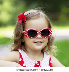 The image of a little girl in fashionable sunglasses