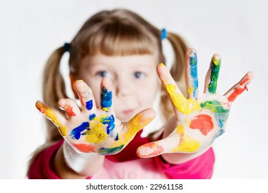 An image of a little girl with her hands in paint